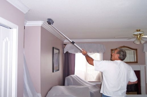 worker from magic mist ceiling cleaning brushing residential ceiling